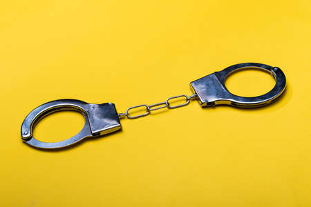 Illegal drug crisis concept showing handcuffs on a yellow background