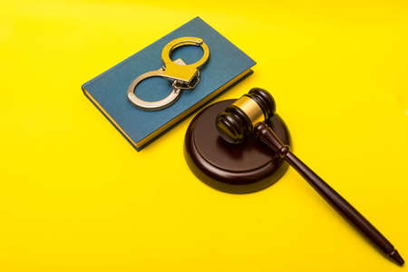 Crime or justice concept showing a gavel with a book of law and handcuffs on a yellow background