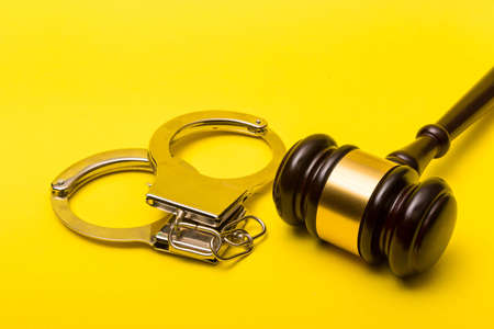 Crime or justice concept showing a gavel on a yellow background with handcuffs