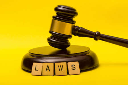 Crime or justice concept showing a gavel on a yellow background and a sign reading laws