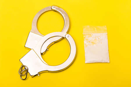 Crime or justice concept showing a pscket of drugs on a yellow background with hancuffs