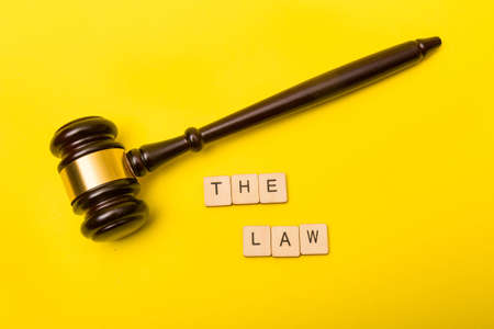 Crime or justice concept showing a gavel on a yellow background with a sign reading the law