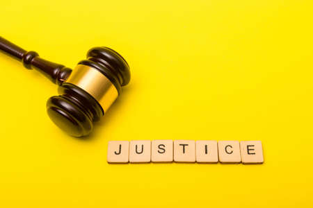 Crime or justice concept showing a gavel on a yellow background with a sign reading justice