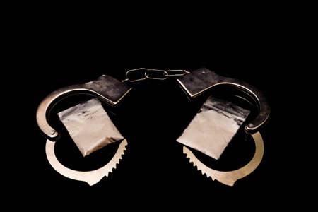 Crime concept showing plastic bags filled with white powder representing drugs and handcuffs on a black background Reklamní fotografie