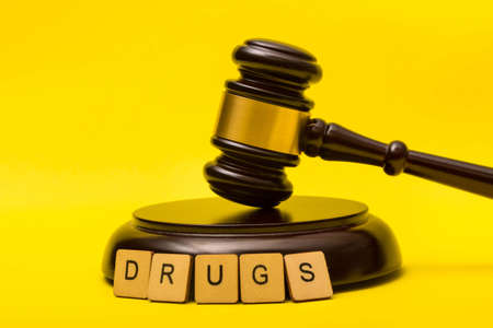 Crime or justice concept showing a gavel on a yellow background and a sign reading drugs