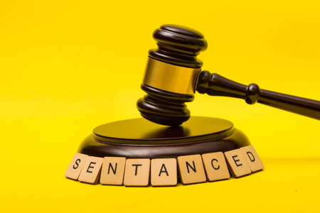 Crime or justice concept showing a gavel on a yellow background with a sign reading sentanced