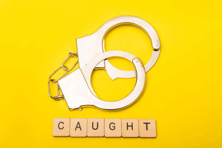Crime or justice concept showing a sign reading caught on a yellow background with handcuffs Reklamní fotografie