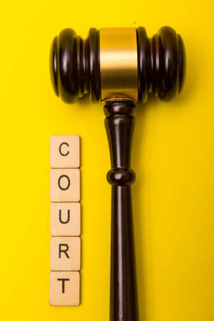 Crime or justice concept showing a gavel on a yellow background with a sign reading court