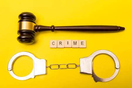 Crime or justice concept showing a gavel on a yellow background with handcuffs and a sign reading crime Reklamní fotografie