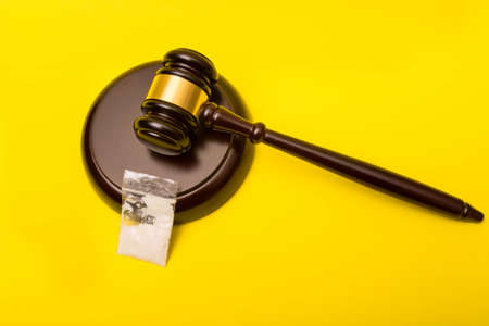 Crime or justice concept showing a gavel on a yellow background and a packet of drugs