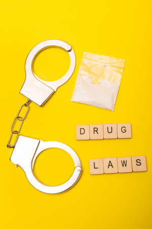 Crime or justice concept showing a packet of drugs on a yellow background with handcuffs and a sign reading drug laws