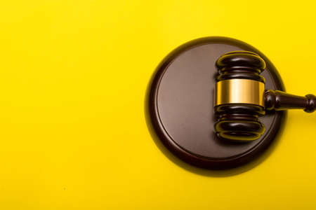 Crime or justice concept showing a gavel on a yellow background Reklamní fotografie