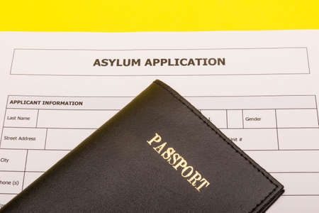 Travel concept showing a passport and an application form for asylum on a yellow background