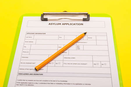 Asylum concept showing an application form for asylum on a yellow background
