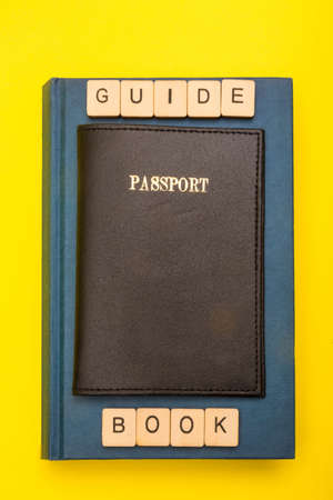 Travel concept showing a passport on a book with a sign reading guide book with a yellow background