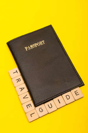 Travel concept showing a passport with a sign reading travel guide on a yellow background