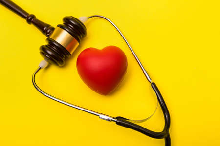 Medical malpractice lawsuit concept showing a heart, a gavel and a stethoscope on a yellow background Reklamní fotografie