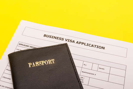 Travel concept showing a passport and an application form for a business visa on a yellow background