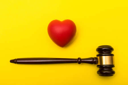 Medical malpractice lawsuit concept showing a gavel and a heart on a yellow background