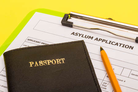 Asylum concept showing an application form for asylum on a yellow background with a pen and a passport