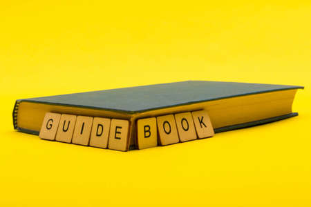 Travel concept showing a book with a sign reading guide book on a yellow background Reklamní fotografie