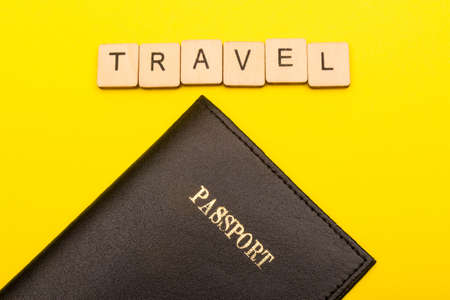 Travel concept showing a passport on a yellow background with a sign reading travel