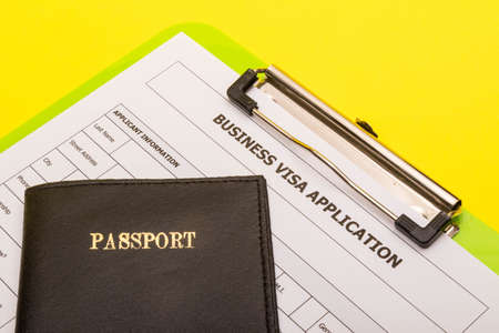 Travel concept showing an application form for a business visa with a passport on a yellow background Reklamní fotografie