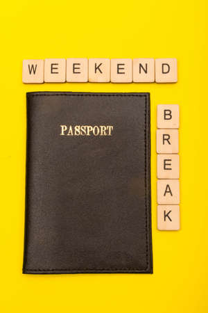 Travel concept showing a passport on a yellow background with a sign reading winter break