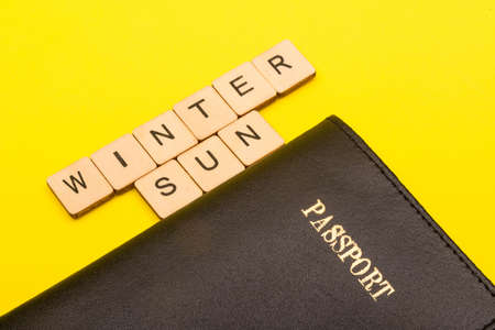 Travel concept showing a passport on a yellow background with a sign reading winter sun Reklamní fotografie