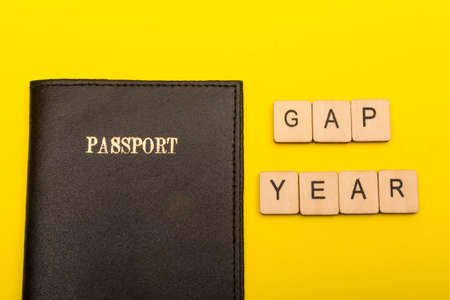 Travel concept showing a passport on a yellow background with a sign reading gap year