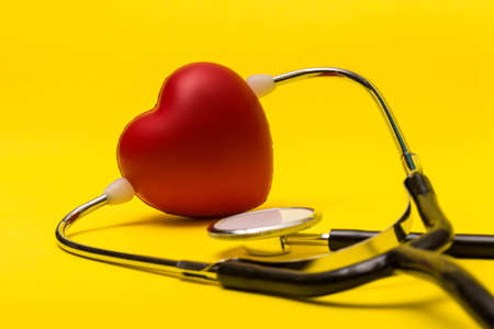 Medical care concept showing a heart and a stethoscope on a yellow background Reklamní fotografie