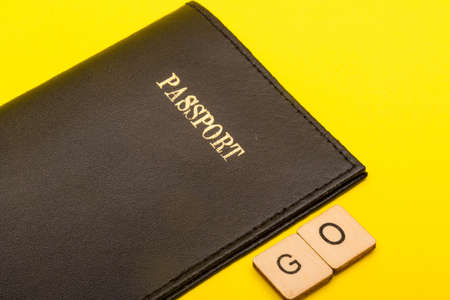 Travel concept showing a passport on a yellow background with a sign reading go