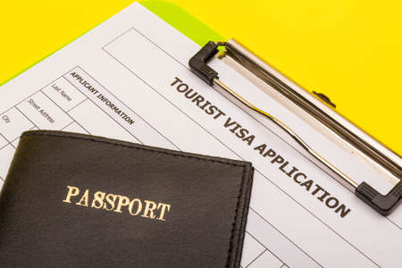 Travel concept showing an application form for a tourist visa with a passport on a yellow background Reklamní fotografie