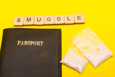 Drug smuggling concept showing a passport on a yellow background with packets of white powder with a sign reading smuggle
