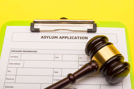 Asylum concept showing an application form for asylum on a yellow background with a gavel