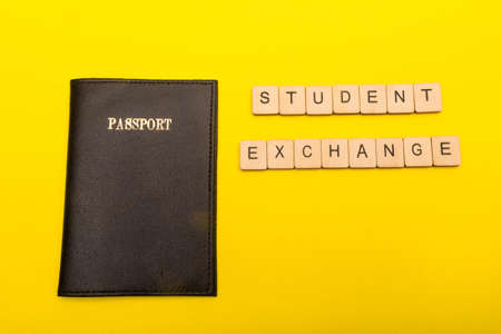 Travel concept showing a passport on a yellow background with a sign reading student exchange