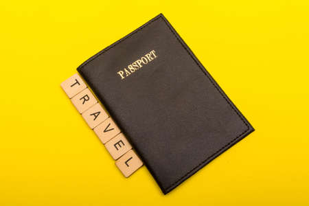 Travel concept showing a passport with a sign reading travel on a yellow background Reklamní fotografie