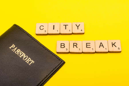 Travel concept showing a passport on a yellow background with a sign reading city break