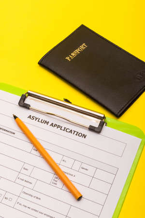Asylum concept showing an application form for asylum on a yellow background with a pen and a passport Reklamní fotografie - 134226276
