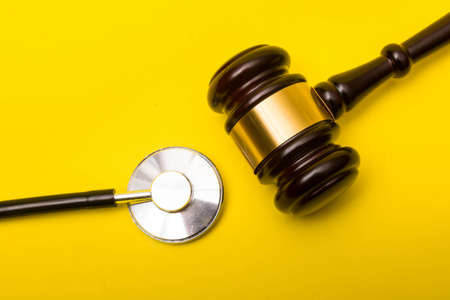 Medical malpractice lawsuit concept showing a gavel and a stethoscope on a yellow background