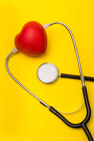 Medical care concept showing a heart and a stethoscope on a yellow background Reklamní fotografie - 134226281