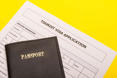 Travel concept showing a passport and an application form for a tourist visa on a yellow background