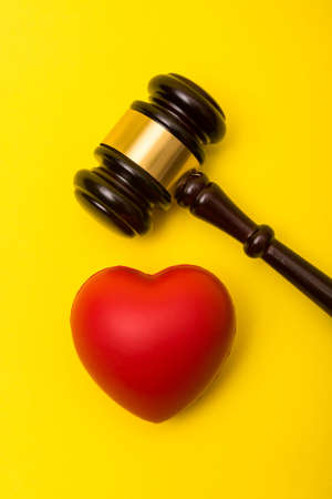 Medical malpractice lawsuit concept showing a gavel and a heart on a yellow background Reklamní fotografie - 134226288