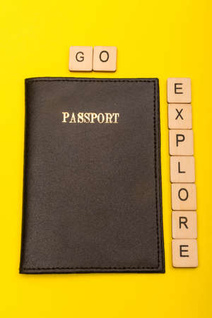 Travel concept showing a passport on a yellow background with a sign reading go explore Reklamní fotografie