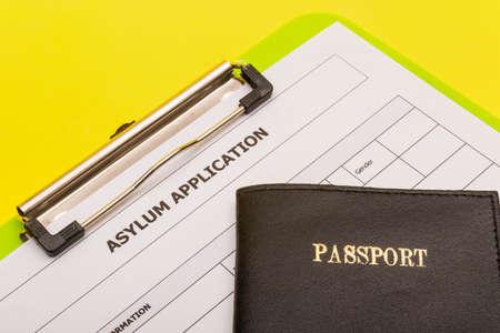 Asylum concept showing an application form for asylum on a yellow background with a passport Reklamní fotografie - 134226289