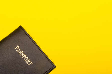 Travel concept showing a passport on a yellow background
