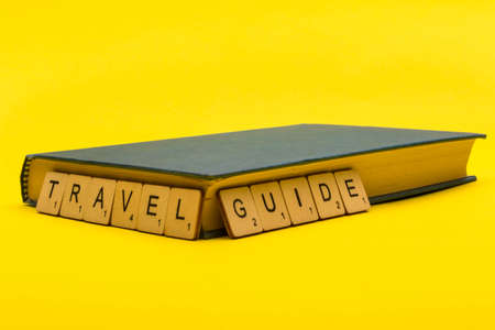Travel concept showing a book with a sign reading travel guide on a yellow background