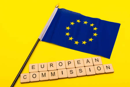 European union concept showing the flag of the EU on a yellow background with a sign reading European Commission Reklamní fotografie - 134424279