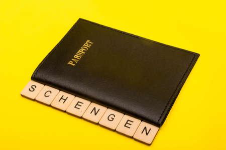 European union concept showing a passport a yellow background with a sign reading Schengen Reklamní fotografie - 134424284