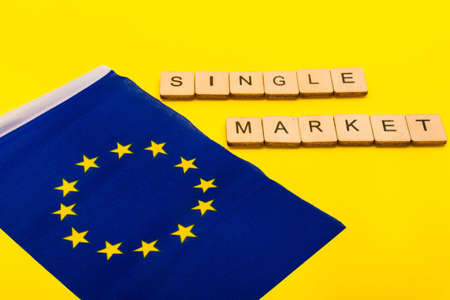 European union concept showing the flag of the EU on a yellow background with a sign reading Single Market Reklamní fotografie - 134424287